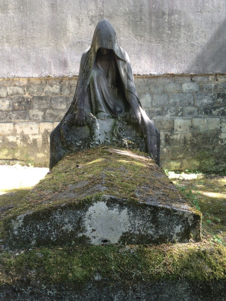 grave with crouched hooded statue