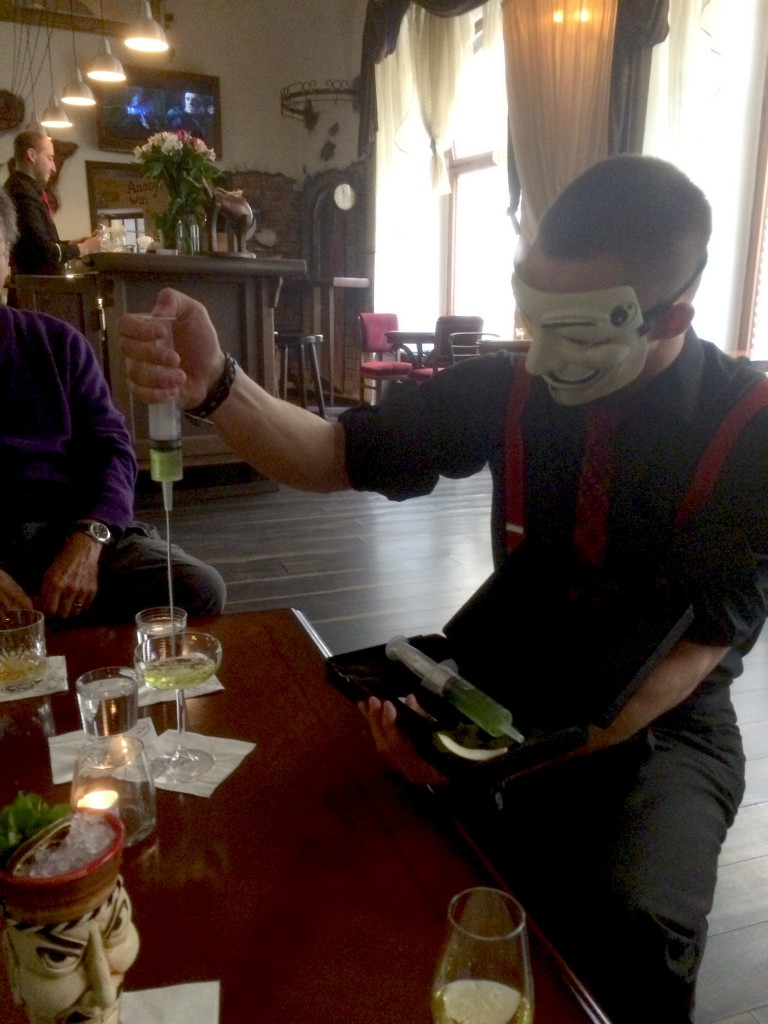 bartender wearing anonymous mask serves drink from needle